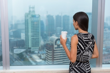 Business woman drinking coffee in office